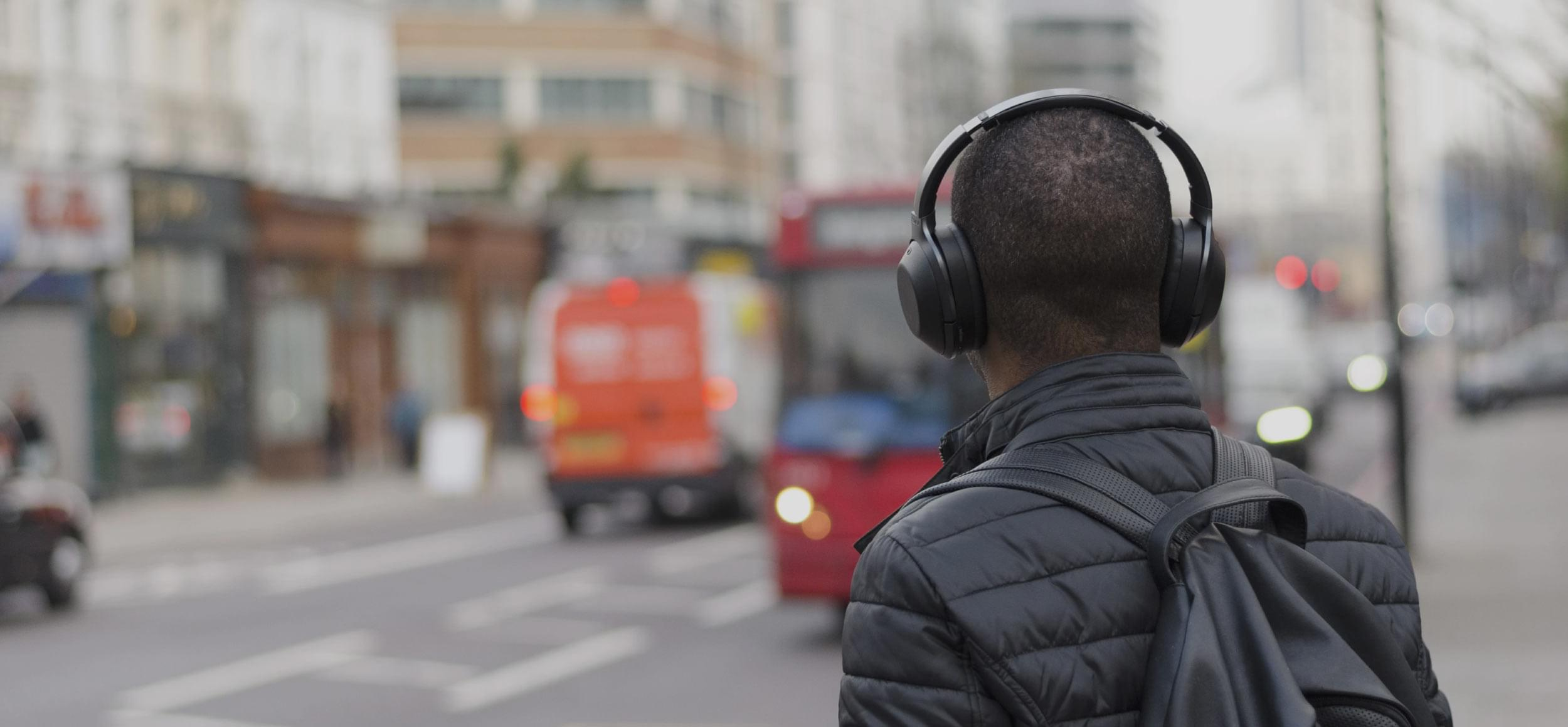 Man wearing headphones looking out on to the street